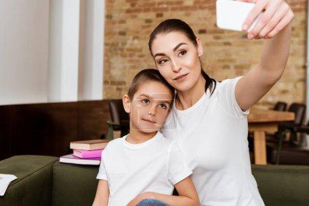 Selektywne skupienie matki i cute syn biorąc selfie ze smartfonem w pobliżu książek na kanapie