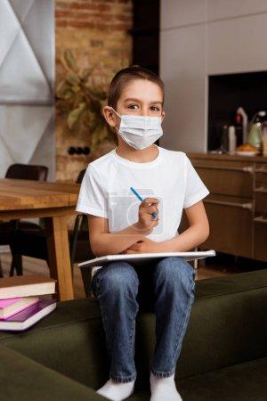 Photo pour Point de mire sélectif d'un enfant en masque médical tenant un carnet de croquis et un crayon près des livres sur le divan - image libre de droit