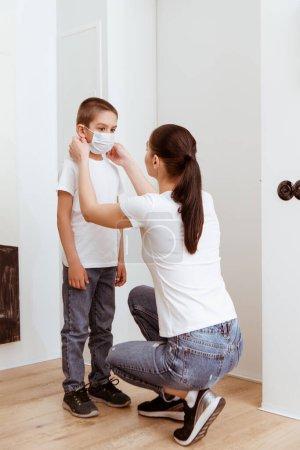 Photo pour Femme portant un masque sur un enfant près de la porte dans le corridor - image libre de droit
