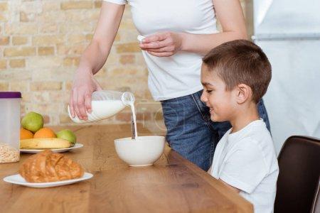 Photo pour Concentration sélective de la mère versant du lait dans un bol avec des céréales près d'un fils souriant dans la cuisine - image libre de droit