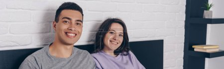 panoramic shot of happy interracial couple smiling at home