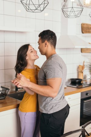 Photo for Happy interracial couple holding hands and looking at each other in kitchen - Royalty Free Image