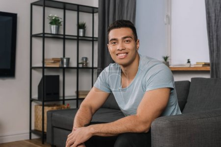 Photo for Happy mixed race man sitting on sofa in living room - Royalty Free Image