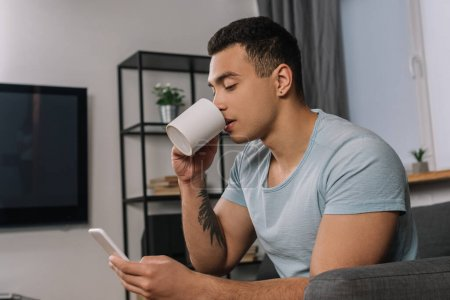 Photo for Handsome mixed race man with tattoo drinking coffee and using smartphone - Royalty Free Image