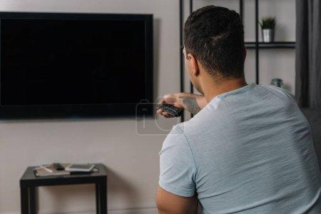 Rückansicht von Mixed Race Mann mit Fernbedienung in der Nähe von Flachbildfernseher mit leerem Bildschirm