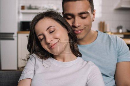 Photo pour Heureux couple interracial avec les yeux fermés souriant à la maison - image libre de droit