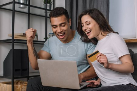 Photo for Happy girl holding credit card near mixed race boyfriend looking at laptop - Royalty Free Image