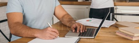 Photo for Panoramic crop of mixed race man writing in notebook near laptop and girl, online study concept - Royalty Free Image