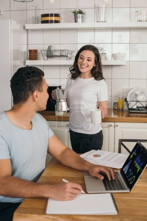 Photo for Selective focus of cheerful girl holding coffee pot and cup near mixed race man, laptop with charts and graphs - Royalty Free Image