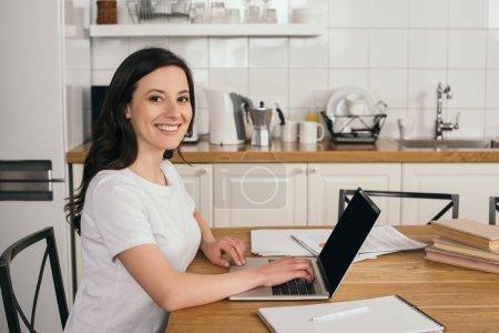 Photo pour Fille gaie en utilisant un ordinateur portable avec écran blanc à la maison, concept d'étude en ligne - image libre de droit
