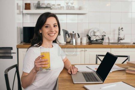 Photo pour Happy woman tenant un verre de jus d'orange près d'un ordinateur portable avec écran vierge - image libre de droit