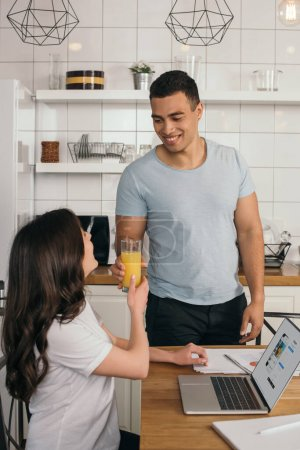 Photo pour KIEV, UKRAINE - MAY 14, 2020 : happy mixed race man giving glass of orange juice to girlfriend near laptop with instagram website - image libre de droit