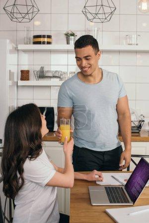 Photo pour Heureux mixte homme de race donnant verre de jus d'orange à petite amie près d'un ordinateur portable avec site médical - image libre de droit