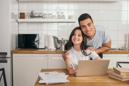 handsome mixed race man hugging happy girlfriend near laptop