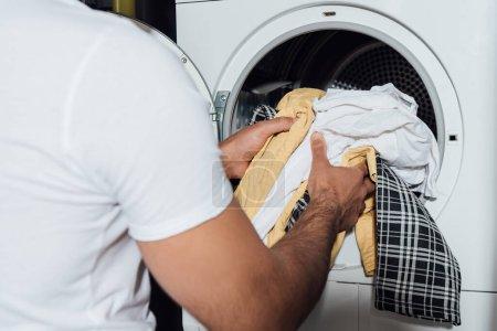 Photo pour Vue recadrée de l'homme mettant linge sale dans la machine à laver moderne - image libre de droit