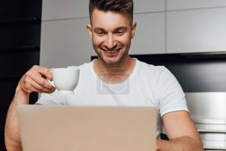 Photo for Selective focus of happy freelancer holding cup of coffee and looking at laptop - Royalty Free Image