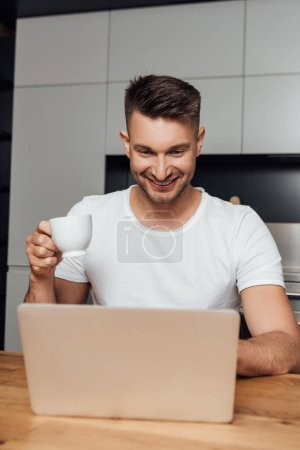 cheerful freelancer holding cup of coffee and looking at laptop