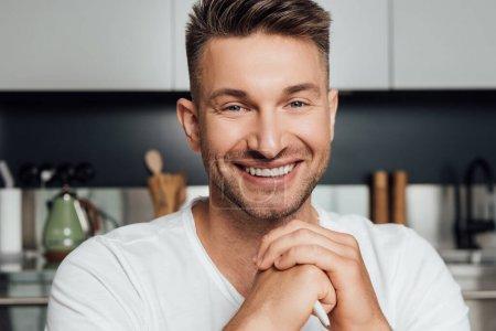 Photo pour Homme heureux avec les mains serrées souriant et regardant la caméra - image libre de droit