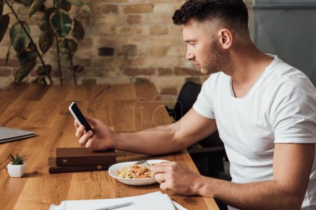 Photo for Side view of man using smartphone while eating noodles near books on kitchen table - Royalty Free Image