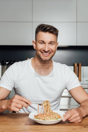 Selective focus of handsome man smiling at camera while eating noodles in kitchen