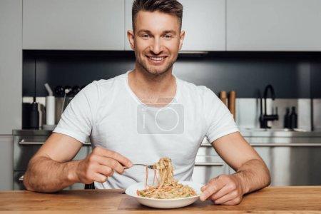 Photo pour Beau homme souriant à la caméra tout en mangeant des nouilles dans la cuisine - image libre de droit