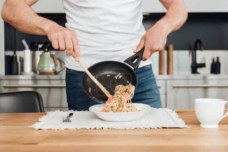 Cropped view of man pouring tasty noodles from frying pan in plate on kitchen table