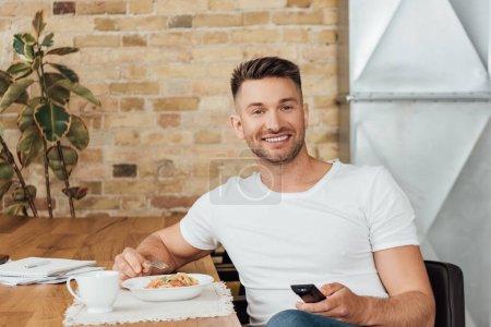 Photo pour Homme souriant tenant télécommande près des nouilles et tasse sur la table de cuisine - image libre de droit