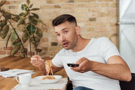 Man clicking channels while eating noodles near papers in kitchen