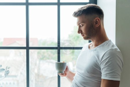 Photo for Side view of handsome man holding cup of coffee while standing near window at home - Royalty Free Image