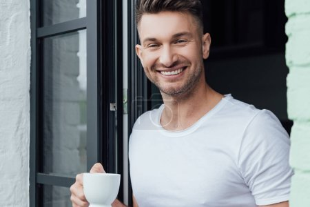 Selective focus of handsome man smiling at camera while holding cup of coffee near terrace door