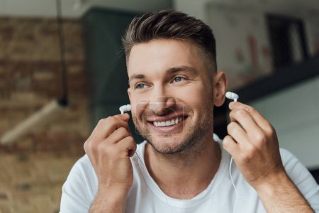 Photo for Smiling man holding earphones in living room - Royalty Free Image