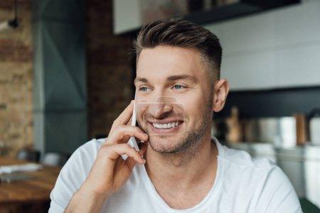 Photo pour Homme souriant parlant sur smartphone dans le salon - image libre de droit