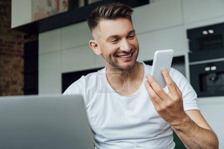 Photo pour Point de mire sélectif d'un pigiste souriant tenant un téléphone intelligent près d'un ordinateur portable à la maison - image libre de droit