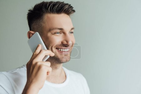 Photo for Handsome man smiling while talking on smartphone isolated on grey - Royalty Free Image