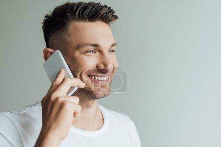 Photo pour Beau homme souriant tout en parlant sur smartphone isolé sur gris - image libre de droit