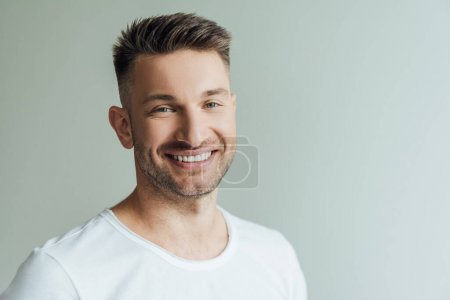 Photo for Handsome man smiling while looking at camera isolated on grey - Royalty Free Image