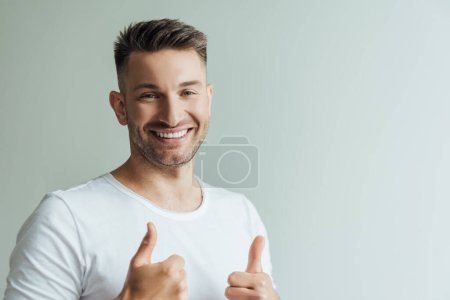 Handsome man smiling at camera and showing thumbs up isolated on grey