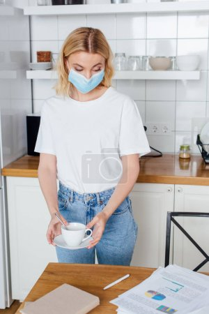 Photo for Young woman in medical mask holding saucer and cup of coffee - Royalty Free Image