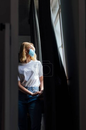 selective focus of young woman in medical mask standing near window at home