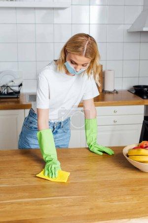Photo pour Une femme dans un masque médical et des gants de latex tenant un chiffon près de la table - image libre de droit
