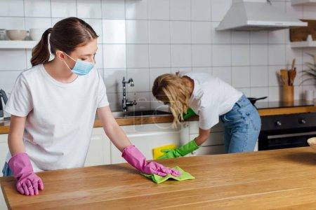 Photo pour Foyer sélectif de la fille dans le masque médical et soeur faisant cuisine travaux ménagers - image libre de droit