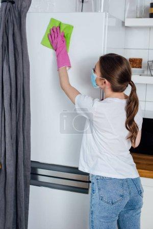 Photo pour Jeune femme en masque médical et gants en caoutchouc tenant chiffon tout en nettoyant le réfrigérateur - image libre de droit
