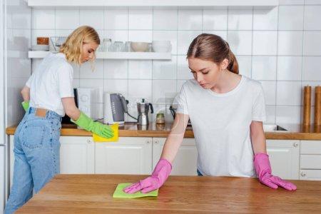 Photo pour Foyer sélectif des sœurs dans des gants en caoutchouc tenant des chiffons tout en nettoyant la cuisine - image libre de droit