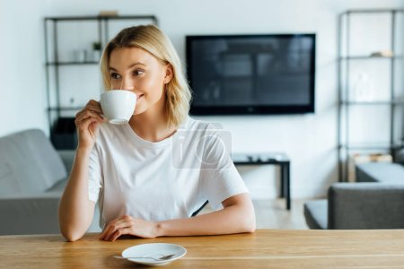 Photo for Cheerful and attractive woman drinking coffee at home - Royalty Free Image