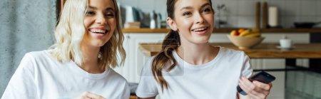 Photo pour Plan panoramique de sœurs gaies regardant un film à la maison - image libre de droit