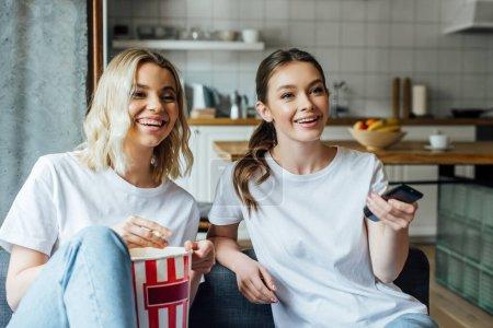 Photo pour Femme heureuse tenant télécommande et regarder le film avec sœur près de savoureux pop-corn - image libre de droit