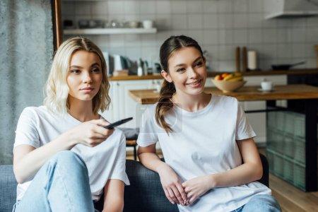 Photo pour Attrayant et jeunes sœurs regarder un film à la maison - image libre de droit