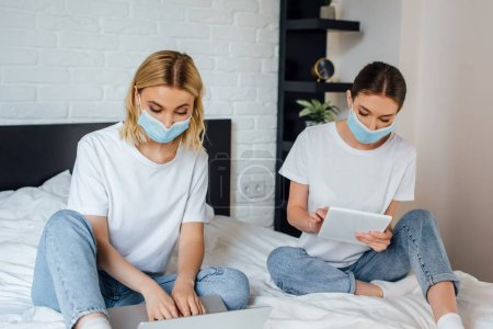 Photo for Sisters in medical masks using laptop and digital tablet on bed - Royalty Free Image