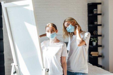 Photo pour Soeurs masquées se tenant près d'un miroir dans une chambre à coucher - image libre de droit