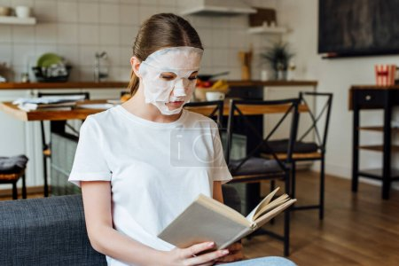 Photo for Selective focus of young woman in face mask reading book at home - Royalty Free Image